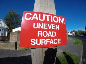 CAUTION! UNEVEN ROAD SURFACE, Sign